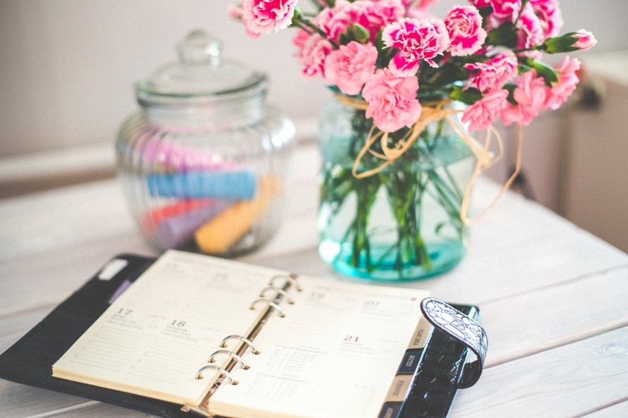 personal-organizer-and-pink-flowers-on-desk