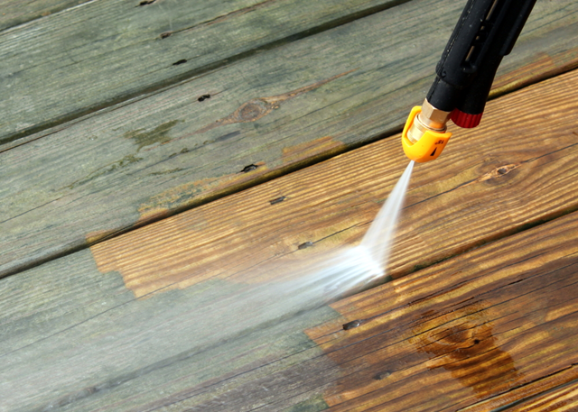 Person using a power washer to clean up his wooden patio