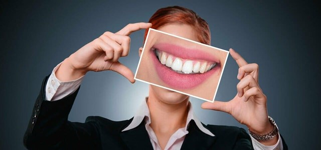 woman holding a photo with mouth with teeth